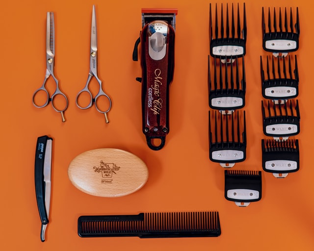 Barber tools laid out on orange background